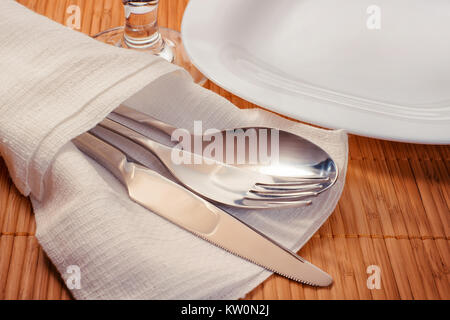 Ajuste de la tabla oficial de estera de bambú. Placa blanca, cubertería y vidrio. Vista lateral de la imagen en tonos cálidos