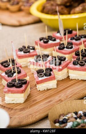 Canapés con rodajas de aceitunas negras, queso y salami blanco sobre una bandeja de madera Foto de stock