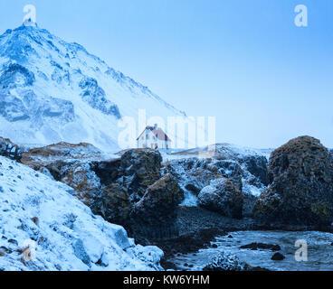 Casa aislada detrás de acantilados cerca de Arnarstapi pueblo al anochecer en invierno, Snaefellsnes, Islandia. Foto de stock