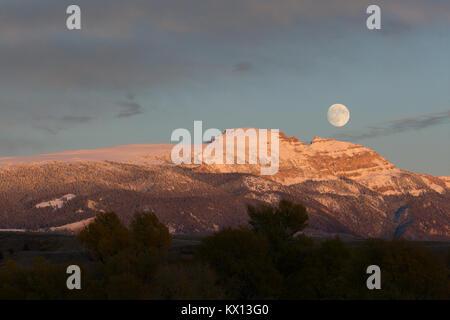 La luna llena elevándose de la India Dormida, aka, Montaña de ovejas de las montañas Gros Ventre. Parque nacional Foto de stock