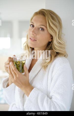 Retrato de atractiva mujer de 40 años en albornoz Beber infusión Foto de stock