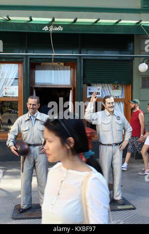 Los turistas cruzar delante de estatuas de piloto de carreras Oscar Gálvez fuera La Biela cafe, Recoleta, Buenos Aires, Argentina
