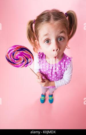 Niña la celebración de big lolly pop. Pigtails cabello modelo de cuatro años de edad con el caramelo de sucker. Niña en un pequeño mundo pensando en grande.