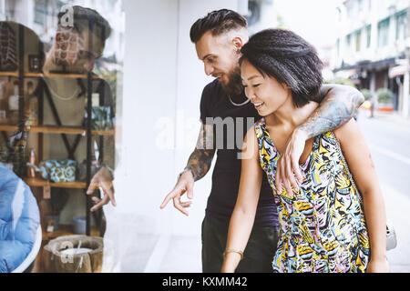 Pluriétnico hipster par mirando y apuntando a la ventana de la tienda,la Concesión francesa de Shanghai, Shanghai, China Foto de stock