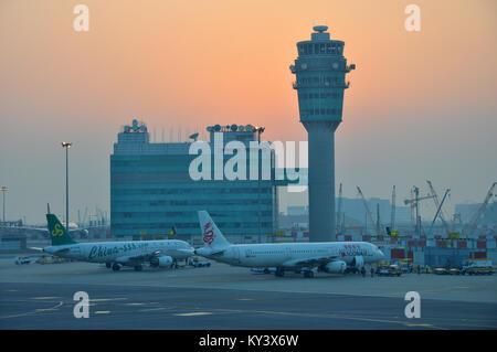 El Aeropuerto Internacional de Hong Kong de la torre de control del tráfico aéreo con Spring Airlines Airbus A320 B-6706 y Dragonair Airbus A321 B-HTH al amanecer. Skyline