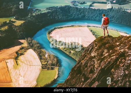 Hombre de viaje sobre las montañas borde del acantilado con mochila aventura concepto de estilo de vida activo el Foto de stock