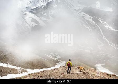 Caminante en camisa verde con mochila y pasear perros en las montañas nevadas en el fondo del cielo neblinoso