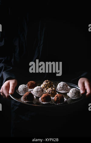 Variedad de trufas de chocolate caseras con cacao en polvo, coco, nueces en vintage bandeja en kid's manos en camisa negra. Fondo oscuro.