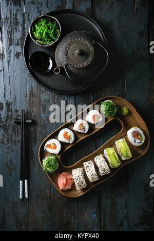 Rollos de sushi casero con salmón, semillas de sésamo y palta sirviendo en placa de madera con rosa encurtido de jengibre, salsa de soja, el wasabi, ensalada de algas, chuletas