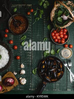 Vista superior de mejillones cocidos con conchas servido en pan con tomate, las hierbas y el vino en la mesa rústica Foto de stock