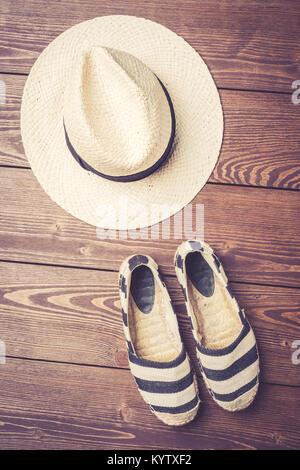 Sombrero de Paja y alpargatas sobre fondo de madera. Vista superior