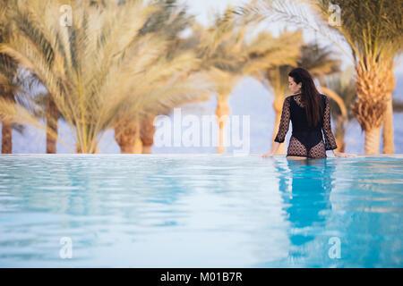 """Dorso de mujer sentada en el borde de la piscina """"infinity"""" que mira sobre el punto de vista del mar y las palmas Foto de stock"""