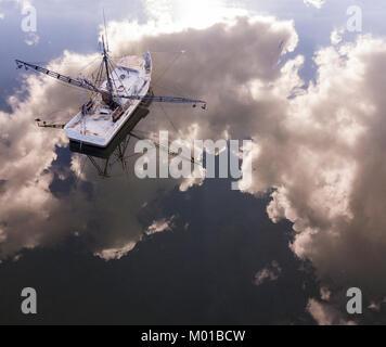 Vista aérea del barco pesquero en Carolina del Sur con el reflejo perfecto del cielo y las nubes en el agua.