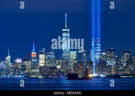 Los dos rayos de luz en el homenaje con skycrapers de Distrito Financiero en la noche. La Lower Manhattan, Ciudad de Nueva York