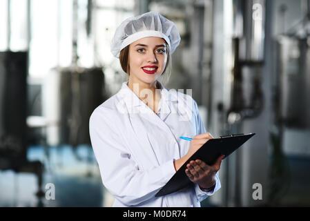 Linda chica en ropa de trabajo blanca hace notas sobre un lápiz sobre una tableta