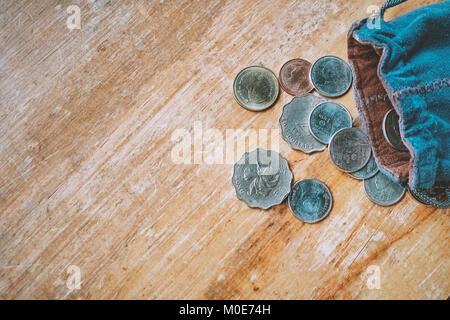 Thai y Hong Kong monedas en bolsa de tela azul sobre la mesa de madera.