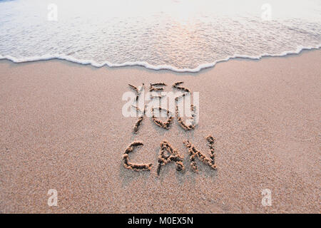 Sí se puede, de motivación concepto inspirador mensaje escrito en la arena de playa.