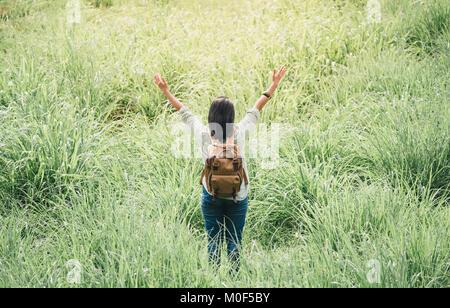 Feliz joven mujer viajero mochilero brazo levantado hasta el cielo, disfrutando de una hermosa de la naturaleza en el campo de hierba verde aire fresco,Libertad wanderlust concepto