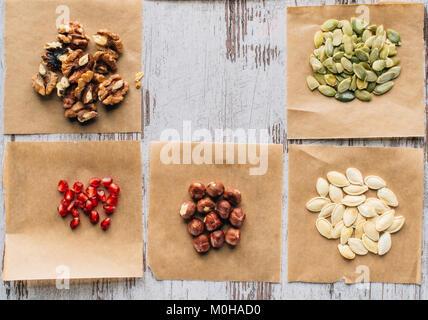 Vista superior de nueces, semillas de calabaza y semillas de granada en la tabla