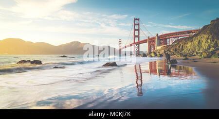 Classic vista panorámica del famoso Golden Gate Bridge visto desde el escénico Baker en la hermosa playa dorada luz del atardecer en un día soleado con el cielo azul