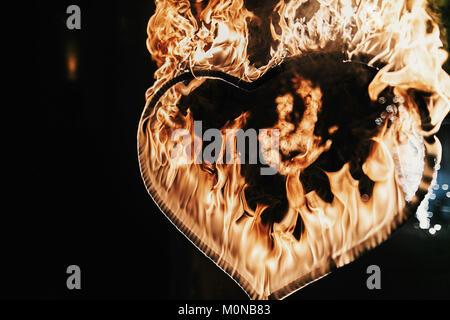 Fuegos artificiales en forma de corazón sobre fondo negro, espectáculo de fuego en la noche. Feliz Día de San Valentín tarjeta corazón ardiente fuego de Bengala. Espacio para el texto. Boda o valen