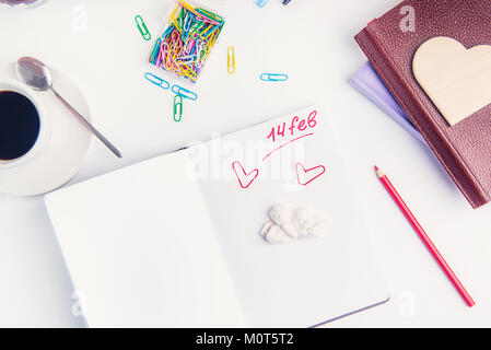 Escritura roja número catorce de febrero, Día de San Valentín texto y ángeles stauette el organizador personal en el lugar de trabajo. Concepto de planificación del día de San Valentín. El enfoque selectivo.