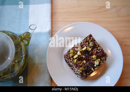 Vista aérea de la comida y la bebida con un vaso tetera de té verde caliente y deliciosa tarta casera o galletas con frutas y nueces sobre la mesa de madera
