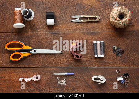 Imagen aérea laicos plana del diseñador de moda artículos concepto de fondo.La vista superior o adaptar accesorios de costura en equipos modernos rústicos de madera marrón en casa