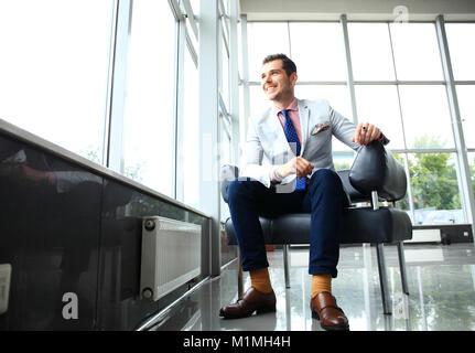Un ángulo bajo la foto de un apuesto joven empresario en un moderno espacio de oficina con grandes ventanales.