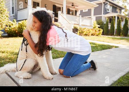 Chica perro caminando a lo largo de la calle suburbana
