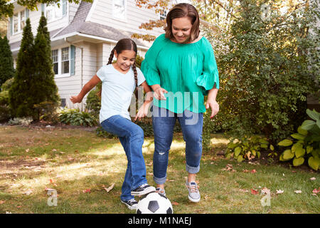 Abuela jugando al fútbol en el jardín con su nieta