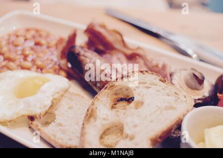 Desayuno con tostadas, huevos fritos, tocino, salchichas, alubias, champiñones y mantequilla - filtro aplicado