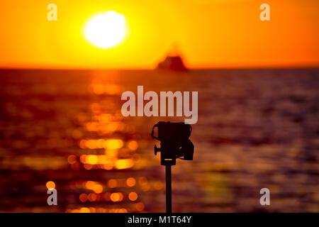 Sunset photograpgy épica con DSLR sobre trípode, fondo borroso Foto de stock