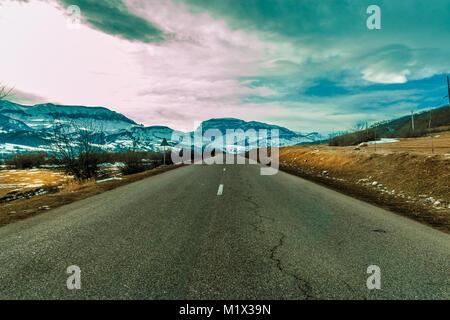 Carretera vacía a la gran montaña con picos nevados.