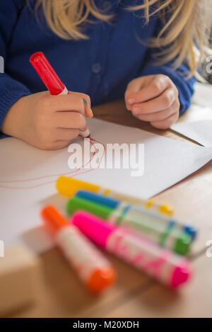 Niña de dibujo con lápices de colores brillantes