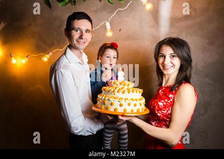 Vacaciones en familia tema childrens cumpleaños y soplar las velas en gran pastel. joven familia de tres personas Foto de stock