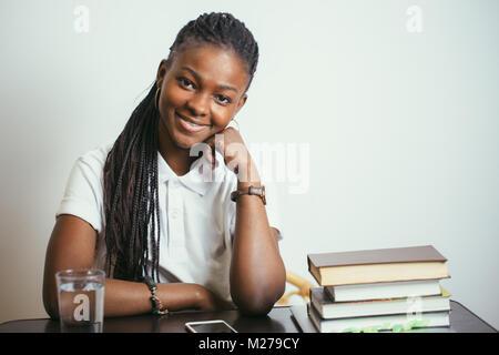 Los jóvenes africanos mujer sentada a la mesa con libros en casa