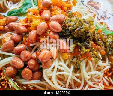 Sopa de fideos picantes con verduras, hierbas, maní y cilantro, popular en la provincia de Yunnan, profundidad de campo, China.
