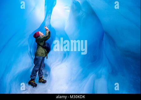 Mujer fotografiando en una cueva de hielo en el glaciar Fox, Isla del Sur, Nueva Zelanda