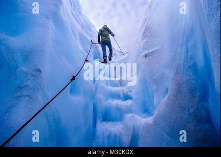 Mujer caminando pasos fuera de una cueva de hielo en el glaciar Fox, Isla del Sur, Nueva Zelanda