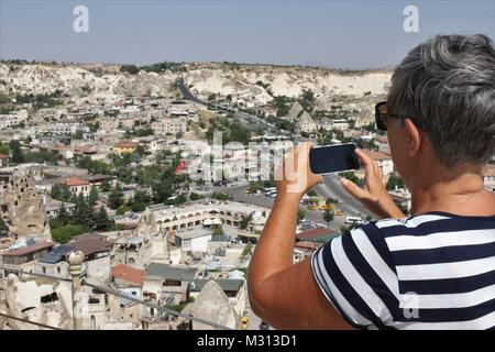 Una señora inglesa turista tomando fotos del impresionante goreme, Capadocia en Turquía