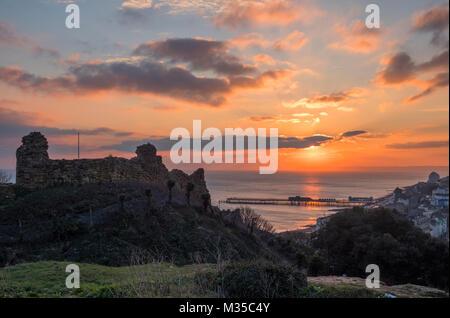 Castillo de Hastings, puesta de sol de invierno con el nuevo muelle, y mirando a la bahía a Beachy Head, East Sussex, Reino Unido