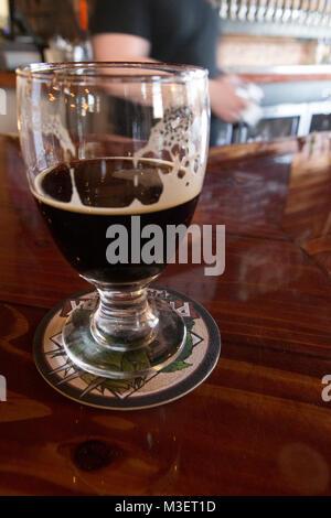 Un medio vaso de cerveza sentado en un bar. Patrones de espuma en el cristal.