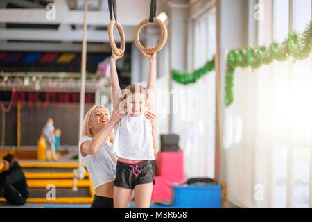Madre ayudando a hija a jugar deportes en anillos de gimnasia