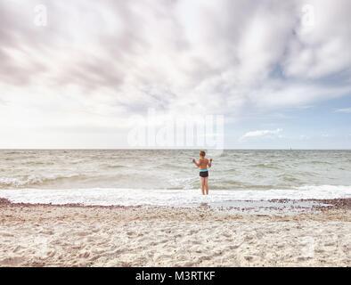 Cabello rubio niño permanecer en frío mar marea. Cabrito en playa de grava de espumosas olas. Día ventoso, nublado cielo azul en seascape
