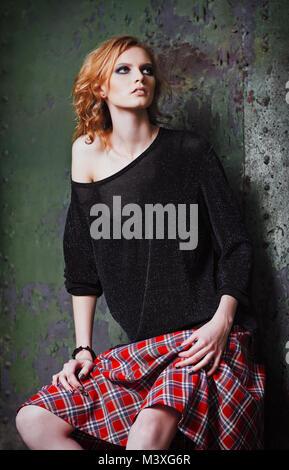 Grunge moda: retrato de una joven y bella chica pelirroja (modelo informal) en el Plaid falda y blusa Foto de stock
