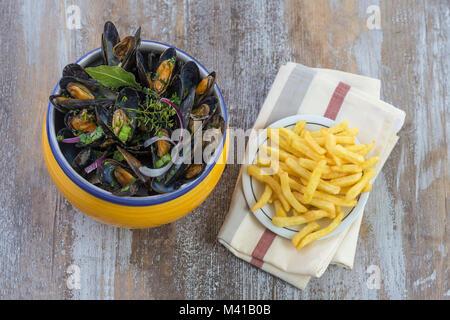 Mejillón Azul francés con hierbas en un recipiente amarillo con papas fritas de vidrio en ramekin servilleta marisco en una placa de madera antecedentes