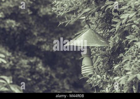 Lámpara Vintage colgado en rama verde de árboles en el jardín exterior en estilo vintage.