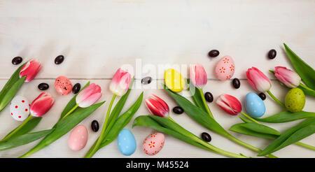 Concepto de Pascua. Tulipanes rosados y huevos de Pascua sobre fondo blanco de madera, espacio para texto, vista superior, banner