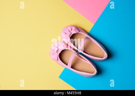 Un alto ángulo de visualización de un par de zapatos de charol rosa sobre fondo amarillo, azul y fondo de color rosa, con algún espacio en blanco